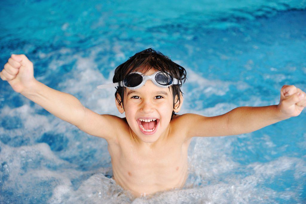 Glad pojke i simbassängen