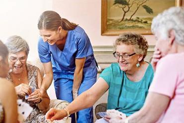 Vårdpersonal med glada pensionärer som spelar kort
