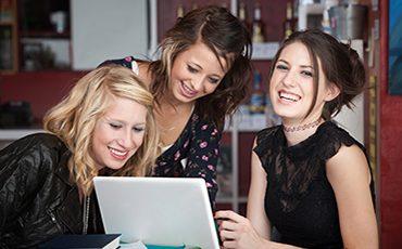 tre glada tjejer vid en dator