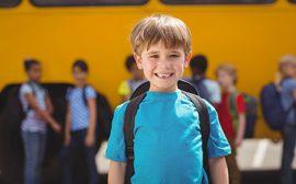 Pojke med ryggsäck framför en skolskjutsbuss