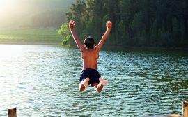 Pojke hoppar i vattnet från en brygga