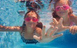 Barn simmar under vattnet i en bassäng