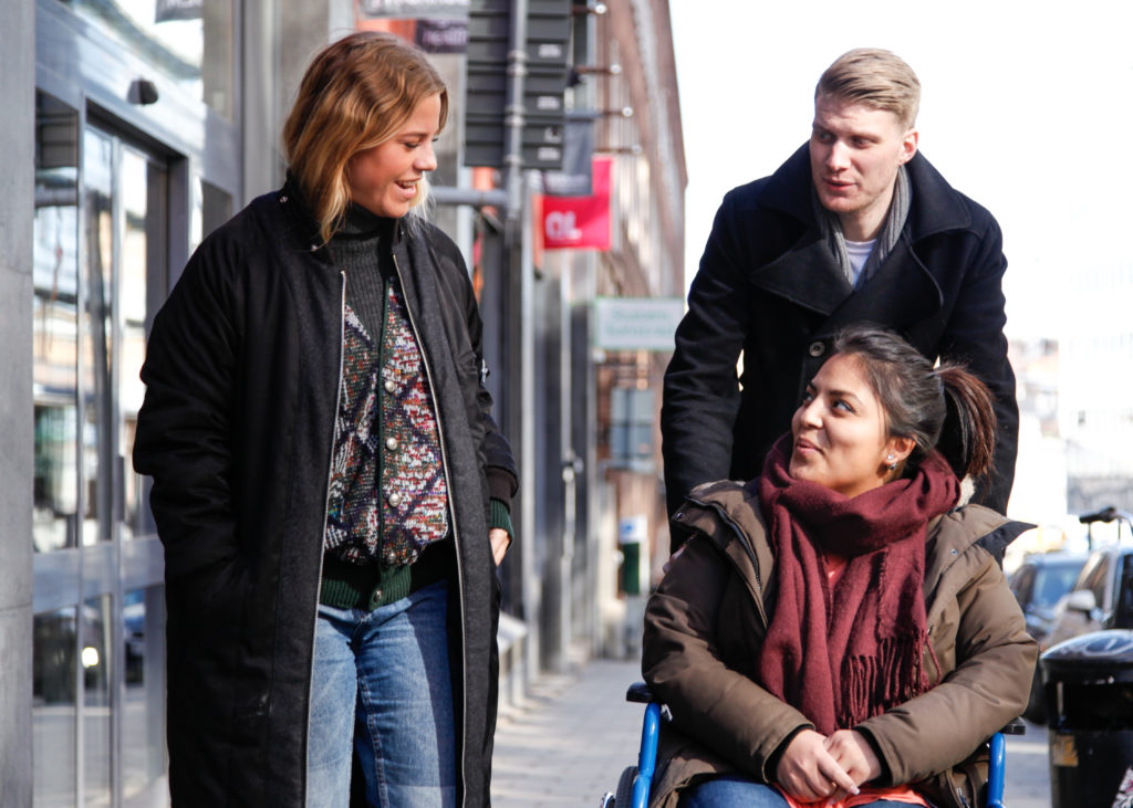 Rullstolsburen person tillsammans med två vänner
