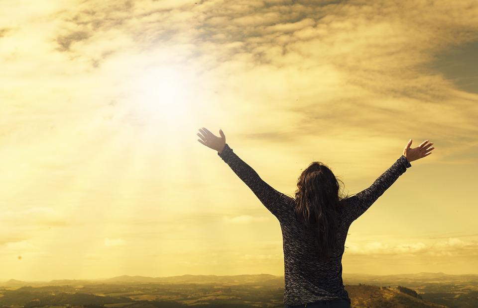 Människa sträcker ut händerna mot skyn