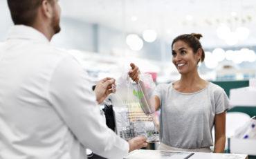 Kvinna lämnar plastpåse fylla av läkemedel till en man.