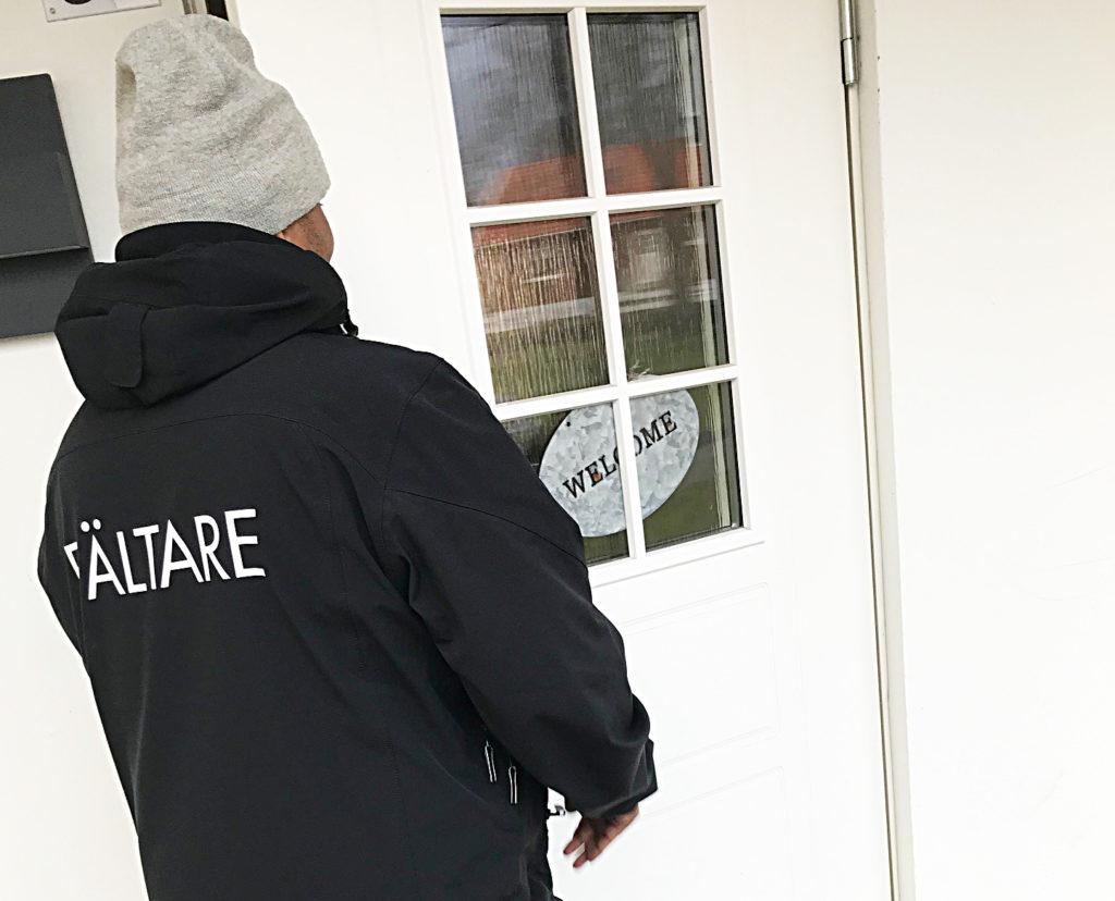Man i svart jacka står vid en dörr.
