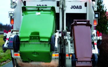Sopbil som tömmer en grön och en brun tunna