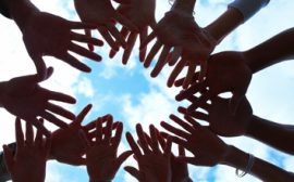 Händer som bildar en cirkel mot himlen