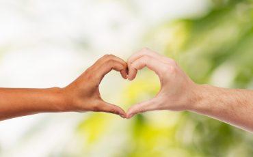 två händer bildar en hjärtsymbol