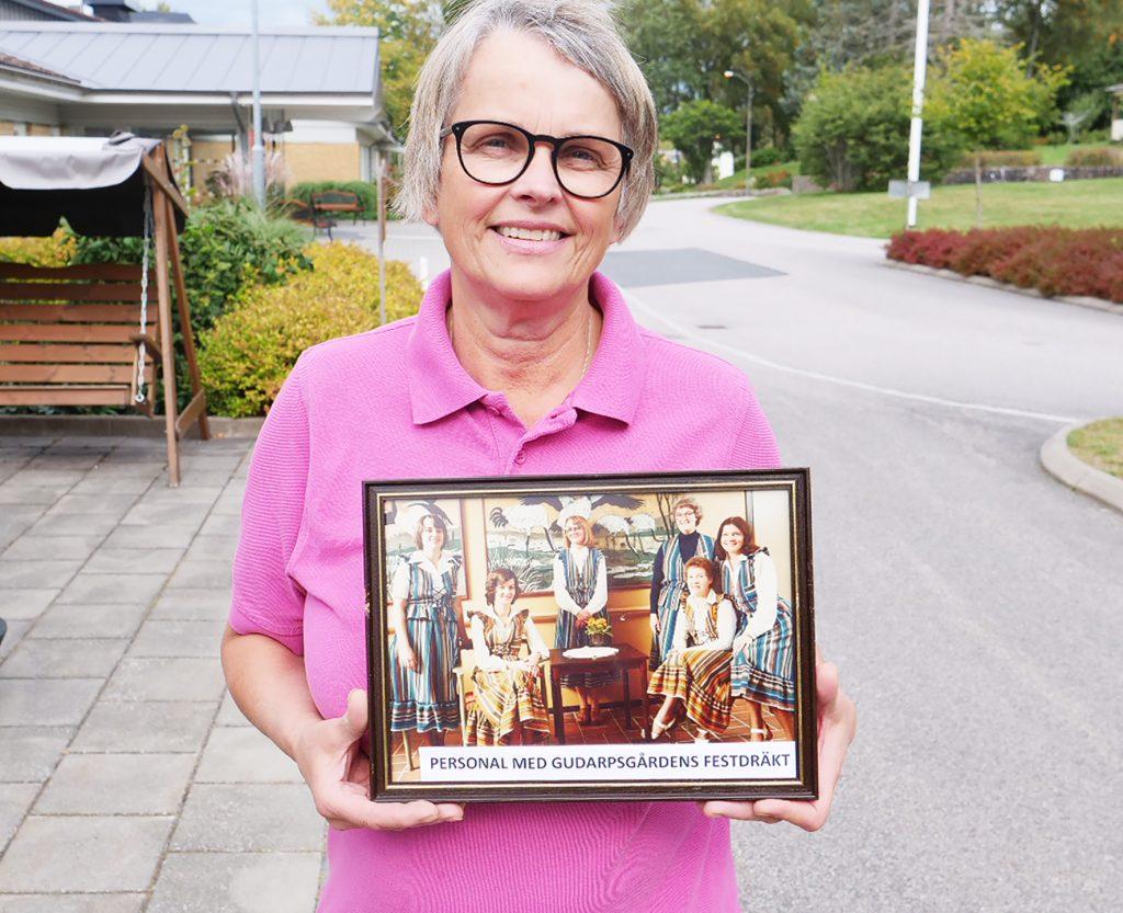 Kvinna håller ett foto framför sig.