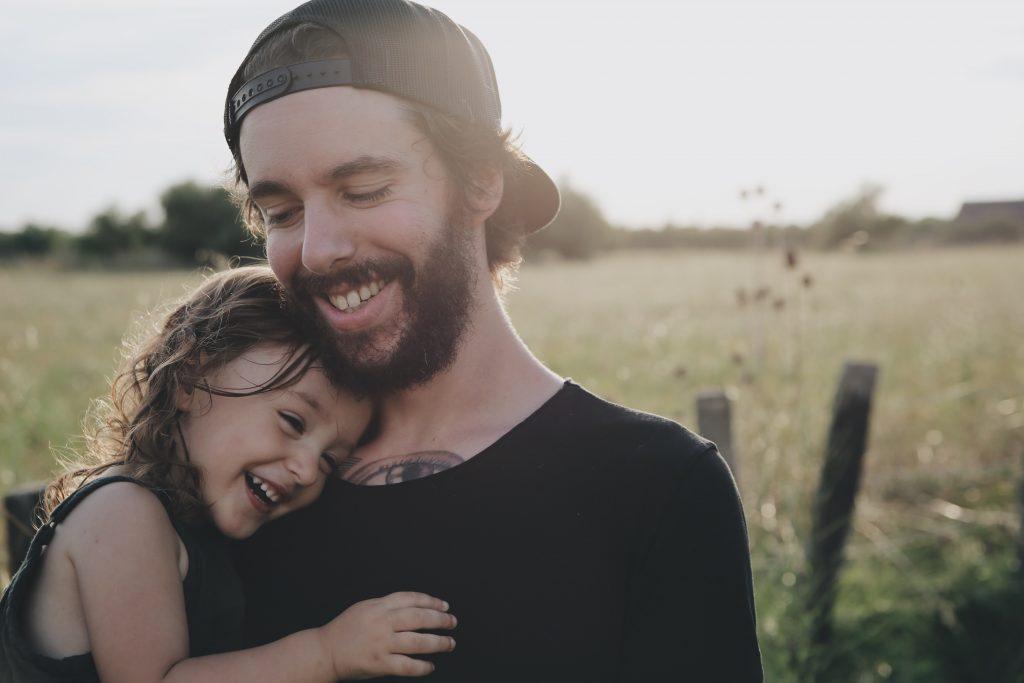 Flicka hänger på pappas axel