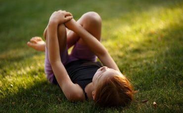 Flicka ligger på gräsmatta