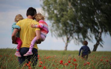 Pappa bär två barn ett tredje barn springer på en äng.
