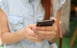 kvinna håller i mobil
