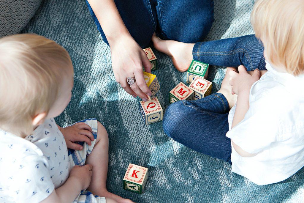Barn som sitter på golvet och leker med klossar