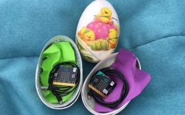 Färgglada ägg med elektronik-innehåll mot dovt blå bakgrund.
