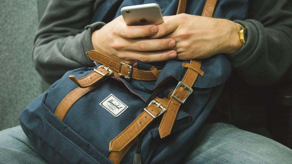 En person håller i en mobil. Händerna vilar mot en ryggsäck
